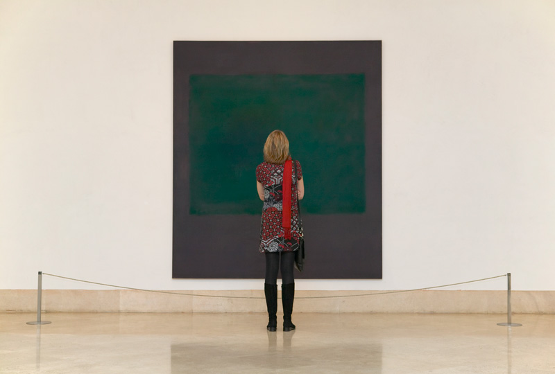 Woman inside a Museum in front of a Mark Rothko picture looking at it.