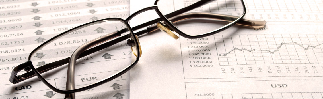 Image of a pair of glasses on top of financial paperwork